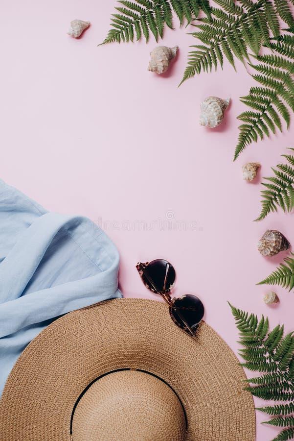 Weibliche Sommermodezusammensetzung mit Bluse, Hut, Sonnenbrille, Farn, Muschel auf rosa Hintergrund stockbilder