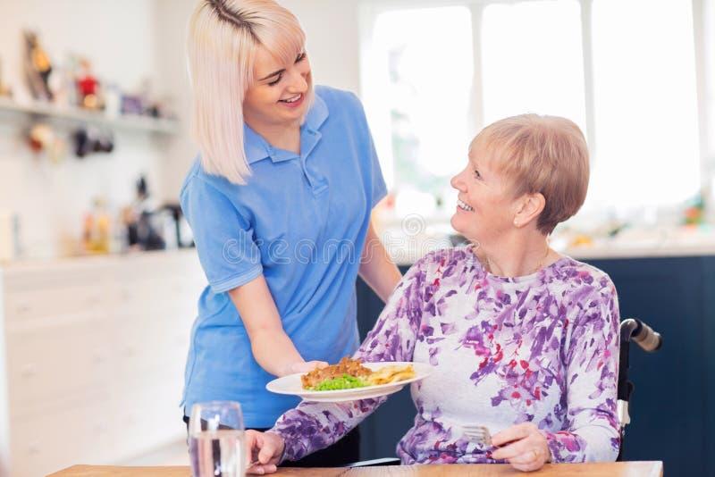 Weibliche Sorgfalt-behilfliche dienende Mahlzeit zur älteren Frau bei Tisch gesetzt im Rollstuhl lizenzfreie stockbilder