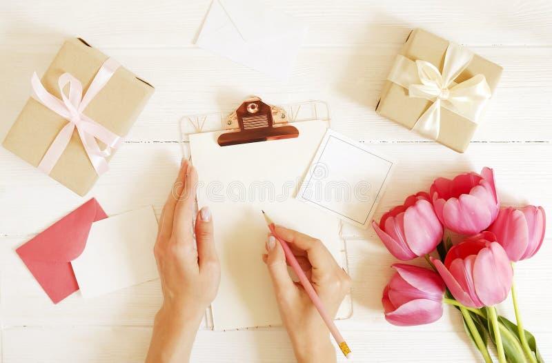 Weibliche Tischplattenzusammensetzungsfrauen-Schreibensgrüße auf leerer Karte bedecken Klemmbrett, rosa Tulpenblumenstrauß, Kraft stockfotos