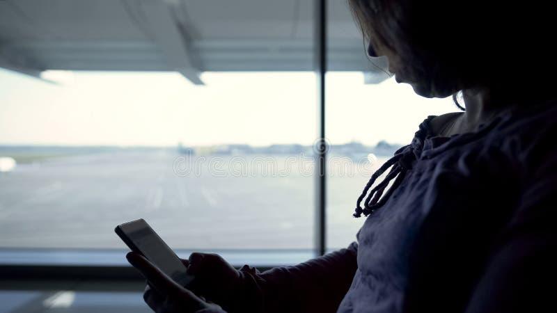 Weibliche touristische Leseon-line-Buch, Warteflug, Zeit im Flughafen verbringend lizenzfreies stockbild