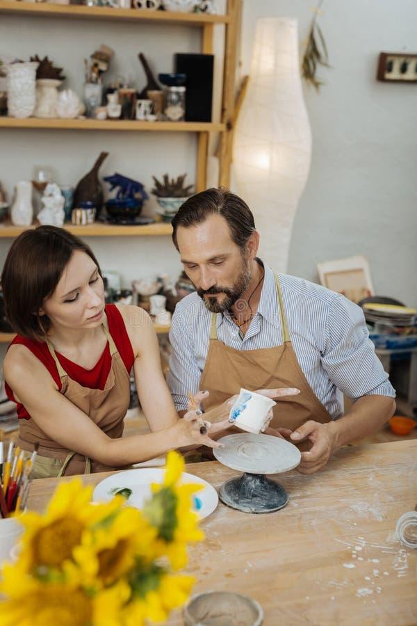 Weibliche und männliche Ceramists, die ihre Arbeit mit Dekorationen beenden lizenzfreie stockbilder