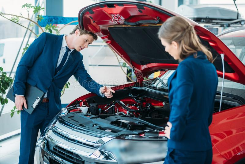 Weibliche und männliche Verkaufsleiter eines Autosalons, der unter Auto schaut stockfotos