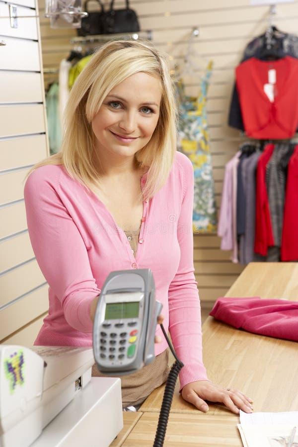 Weibliche Verkäufe behilflich im Bekleidungsgeschäft stockfotografie