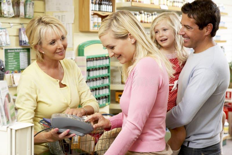 Weibliche Verkäufe behilflich im Biokostspeicher stockfoto