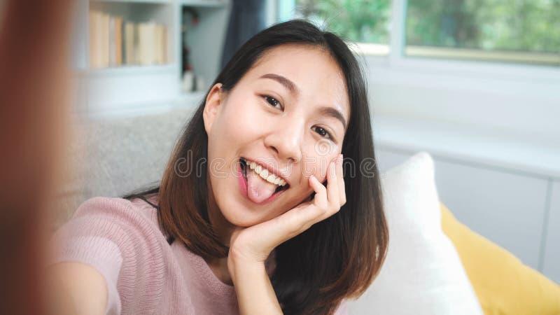 Weibliche Verwendung von Smartphones, die Vlog-Videos in sozialen Medien im Wohnzimmer abspielen lizenzfreies stockbild