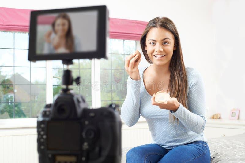 Weibliche Vlogger-Aufnahme-Sendung bilden ungefähr im Schlafzimmer stockfotografie