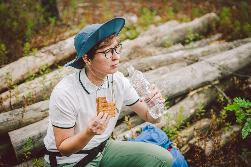 Weibliche Wanderer essen Sandwich in der Natur Touristinnen, die zum Picknick frühstücken oder zu Mittag essen, warme Sandwiches  lizenzfreie stockfotos