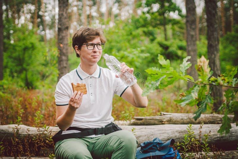 Weibliche Wanderer essen Sandwich in der Natur Touristinnen, die zum Picknick frühstücken oder zu Mittag essen, warme Sandwiches  lizenzfreie stockbilder