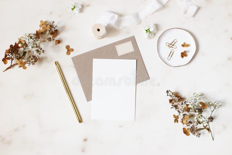 Weibliche Winterhochzeit, Geburtstagsbriefpapier-Modellszene Leere Grußkarte, Kraftpapier-Umschlag, goldener Stift, trocken stockfotografie