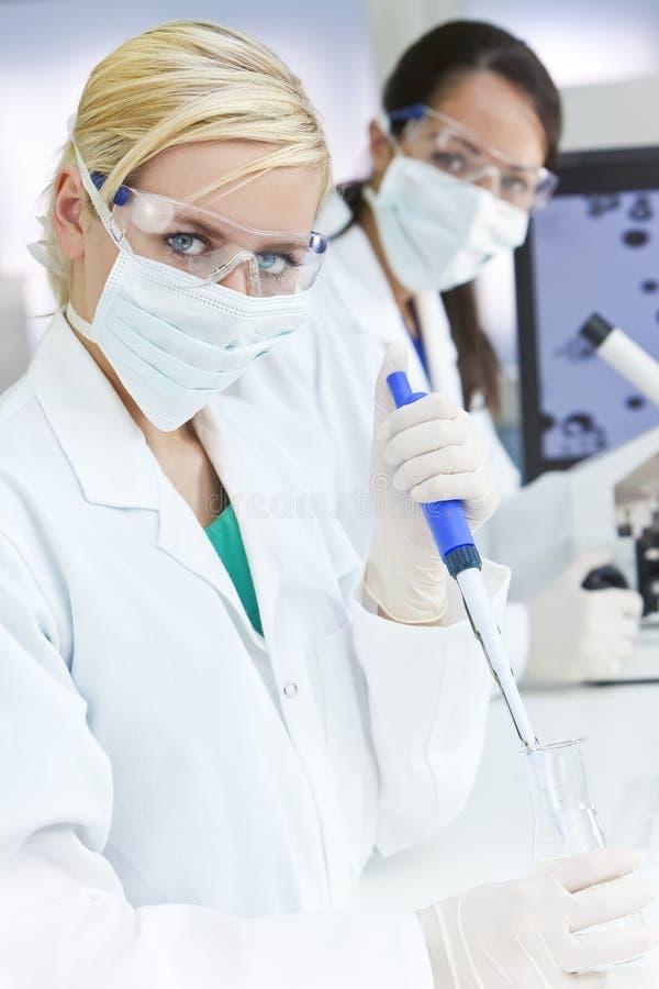 Weibliche Wissenschaftler-Pipette u. Flasche im Labor lizenzfreie stockfotos