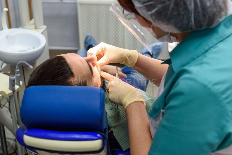 Weibliche Zahnärzte, die an jungem männlichem Patienten arbeiten Zahnarzt ` s Büro lizenzfreie stockbilder