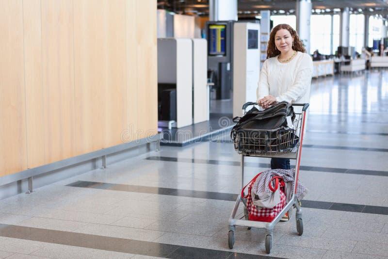 Weibliche ziehende Gepäckhandkarre in der Flughafenhalle lizenzfreie stockfotos