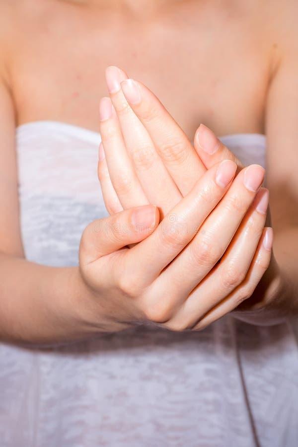 Weibliche zutreffende Feuchtigkeitscreme zu ihren Händen stockfoto
