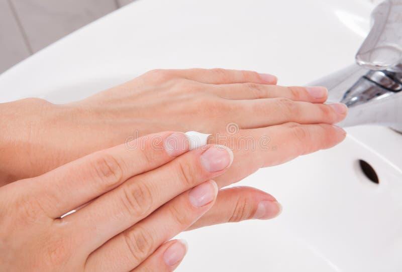 Weibliche zutreffende Feuchtigkeitscreme zur Hand lizenzfreies stockbild