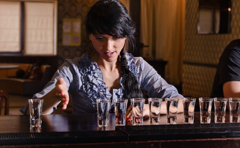 Weiblicher Alkoholiker, der eine Reihe von Schüssen niederwirft lizenzfreie stockfotos