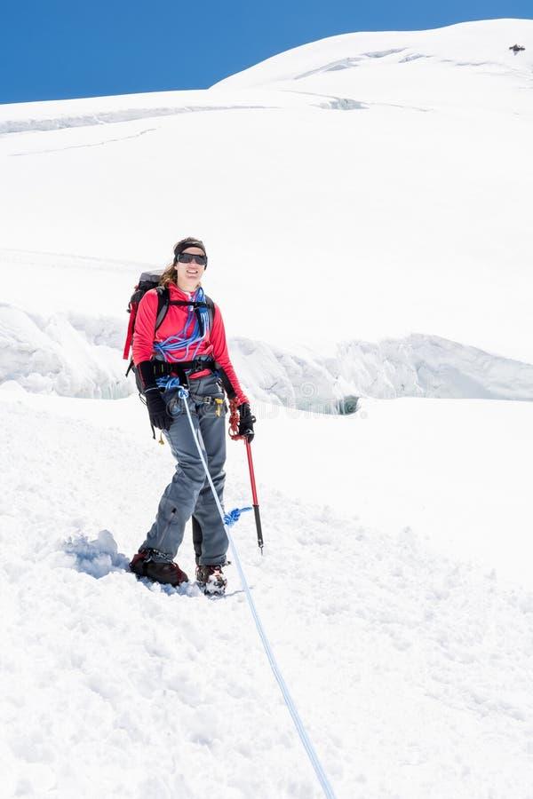 Weiblicher Alpinist, der auf Gletscher steht lizenzfreie stockfotografie