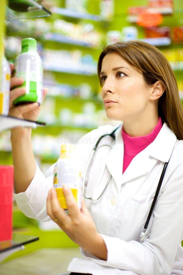 Weiblicher Apotheker, der mit Medizin in der Apotheke arbeitet lizenzfreie stockfotografie