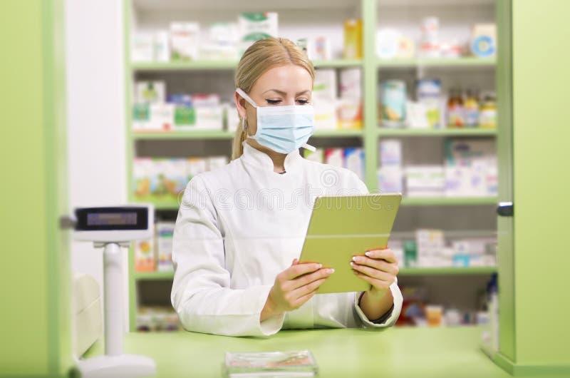 Weiblicher Apotheker mit der chirurgischen Maske, die Tablette hält stockbilder