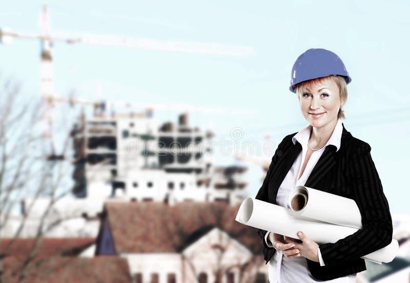 Weiblicher Architekt, der blueprintsFemale Architekten im Bau hält Pläne auf dem Hintergrund eines Hauses hält lizenzfreies stockbild