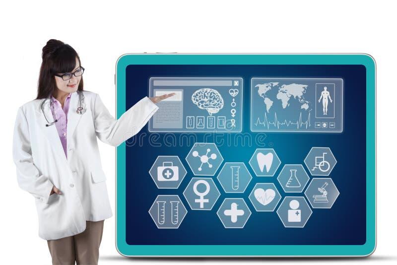 Weiblicher Arzt, der medizinische Symbole zeigt stockfoto