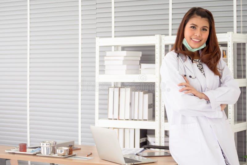 Weiblicher Arzt mit Stethoskopstellung und kreuzte ihre Arme stockfoto