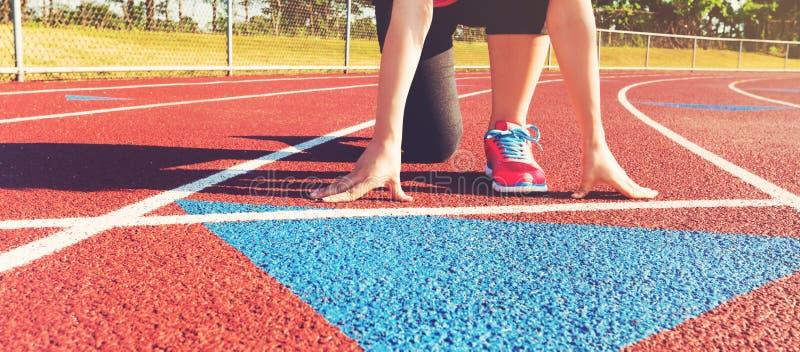 Weiblicher Athlet auf der Anfangszeile einer Stadionsbahn stockbild