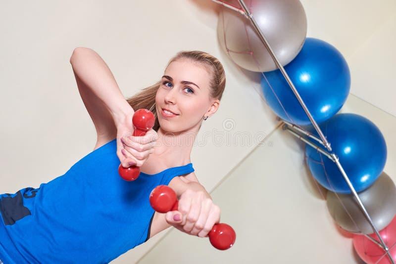 Weiblicher Athlet, der Übung mit Dummkopf tut Konzept der Gesundheit und der Körperpflege lizenzfreie stockfotografie