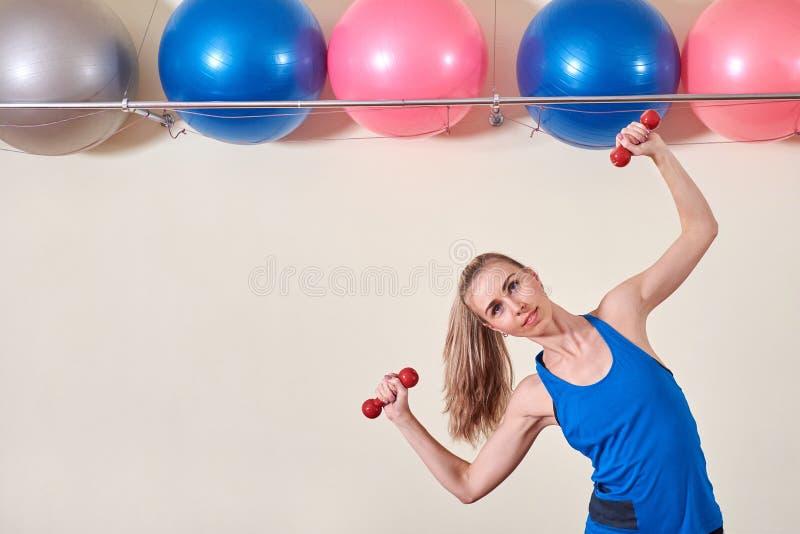 Weiblicher Athlet, der Übung mit Dummkopf tut Kopieren Sie Platz Konzept der Gesundheit und der Körperpflege stockfotografie