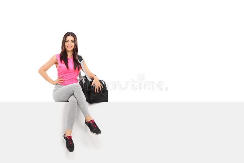 Weiblicher Athlet, der auf einer Platte sitzt stockbilder