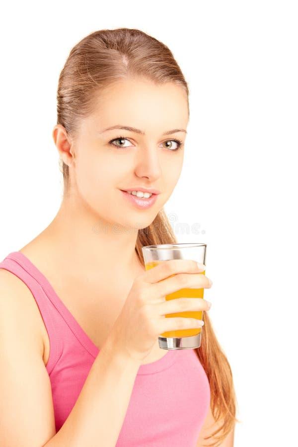 Weiblicher Athlet, der ein Glas Orangensaft, nachher erneuernd hält lizenzfreie stockbilder