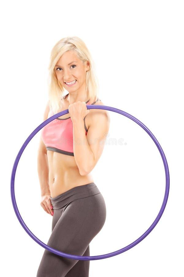 Weiblicher Athlet, der ein Plastik-hula Band hält stockbild