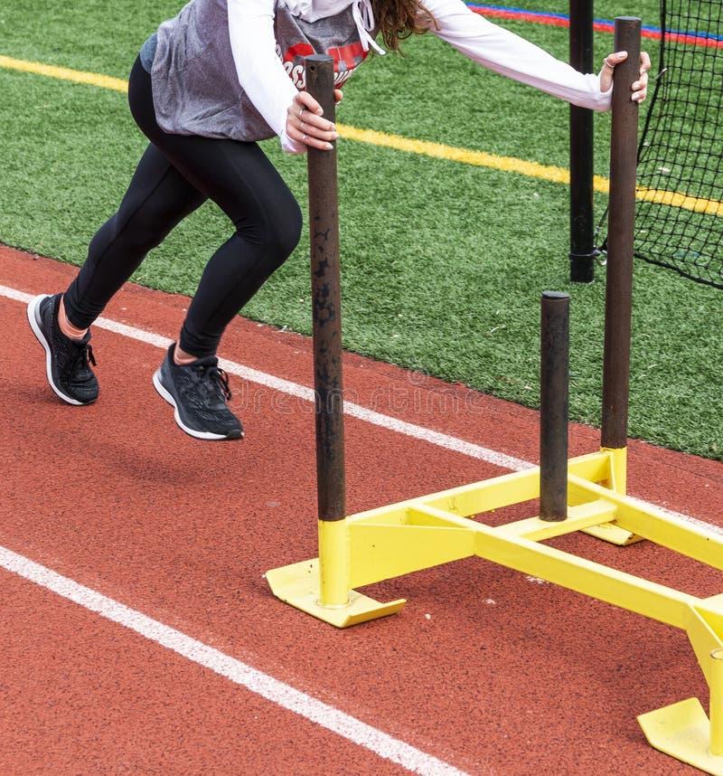 Weiblicher Athlet, der gelben Schlitten auf roter Bahn drückt lizenzfreies stockbild