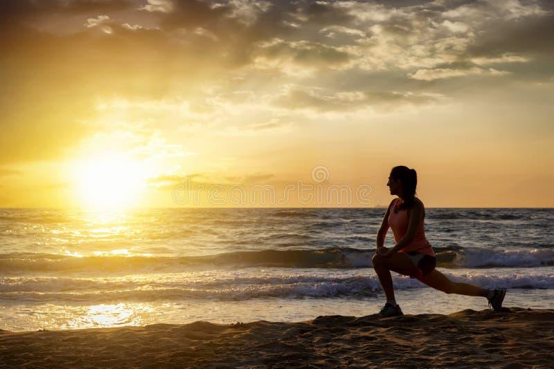 Weiblicher Athlet führt ihre Ausdehnungen auf einem Strand durch stockbild