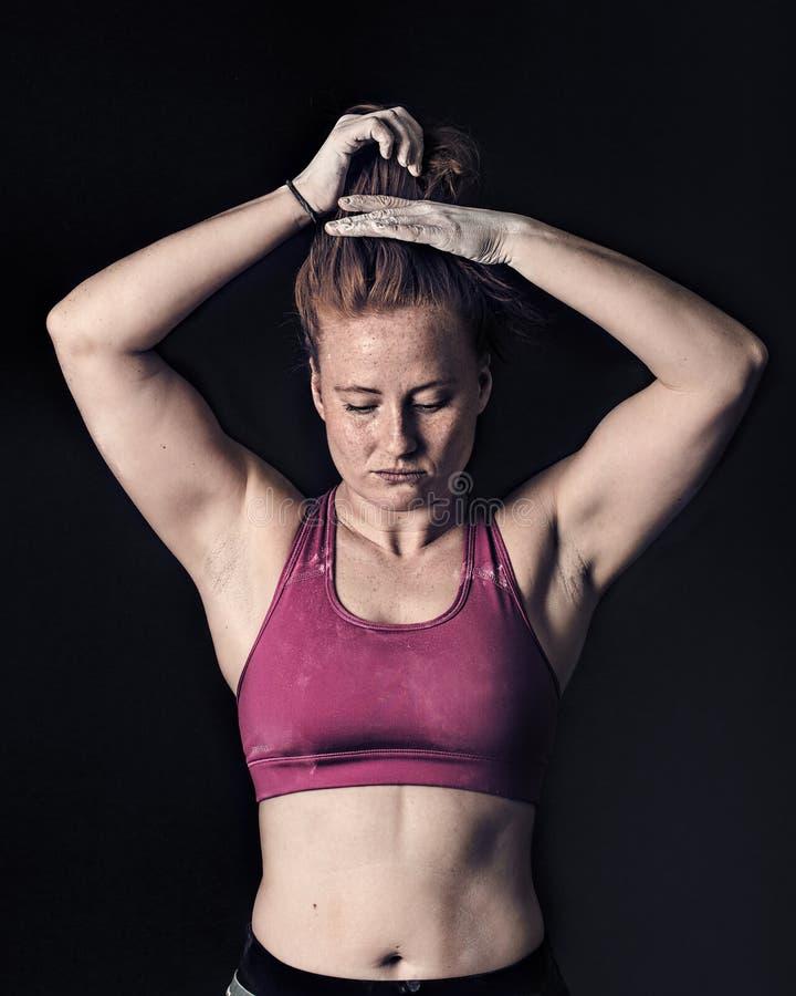 Weiblicher Athlet Tying Hair Sportlerin-dunkle kiesige Stärke u. Bestimmung stockfotografie