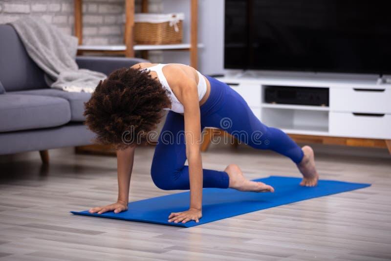 Weiblicher Athleten-Exercising On Fitness-Matte lizenzfreie stockfotografie