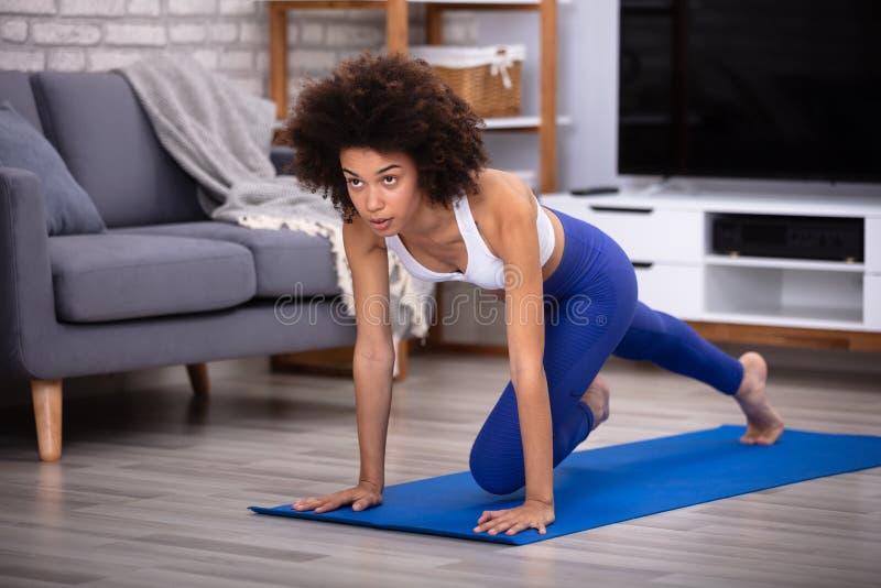 Weiblicher Athleten-Exercising On Fitness-Matte stockfotografie