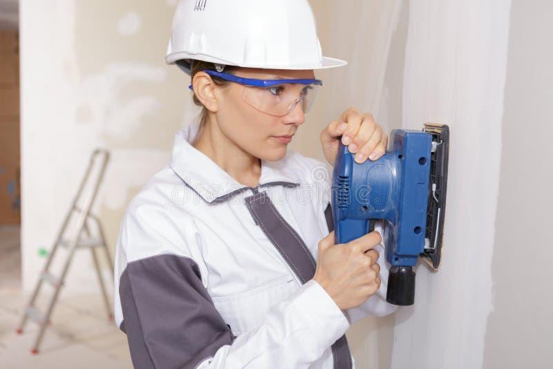 Weiblicher Auftragnehmer des Porträts, der Sandpapierschleifmaschine auf Gipskartonwand verwendet lizenzfreies stockbild
