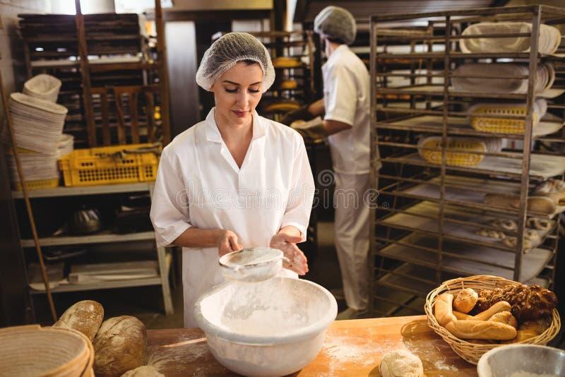 Weiblicher Bäcker, der Mehl durch ein Sieb siebt lizenzfreie stockbilder