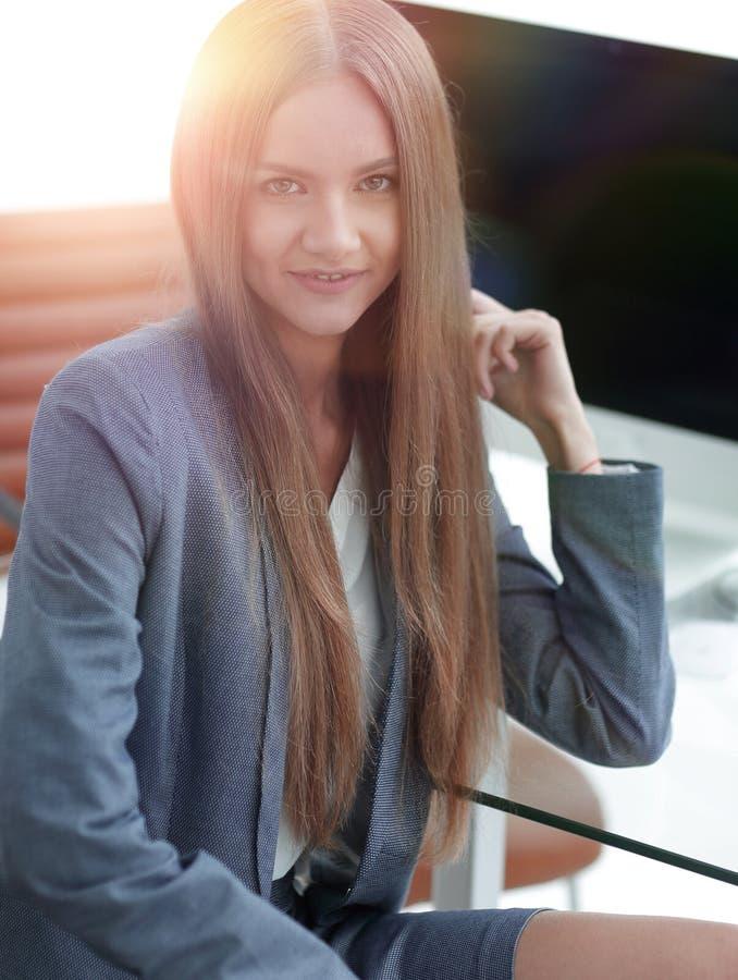 Weiblicher Büroangestellter, der an einem Schreibtisch sitzt lizenzfreies stockbild