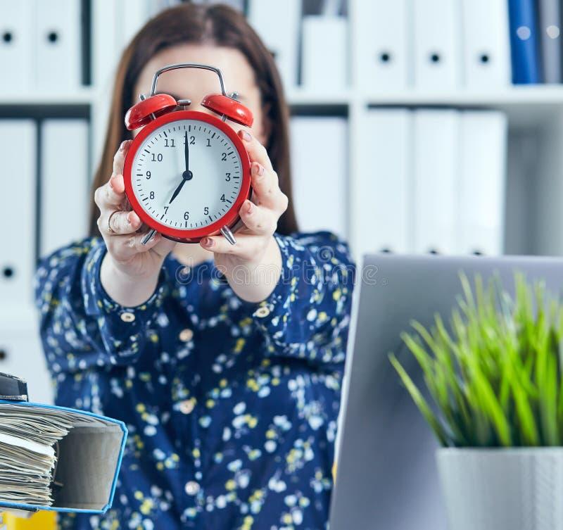 Weiblicher Büroangestellter, der einen großen roten Wecker vor ihrem Gesicht hält lizenzfreies stockbild