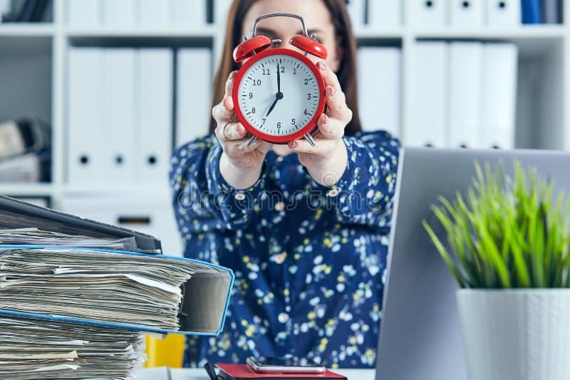 Weiblicher Büroangestellter, der einen großen roten Wecker vor ihrem Gesicht hält stockfotografie