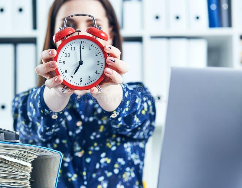 Weiblicher Büroangestellter, der einen großen roten Wecker vor ihrem Gesicht hält stockbilder