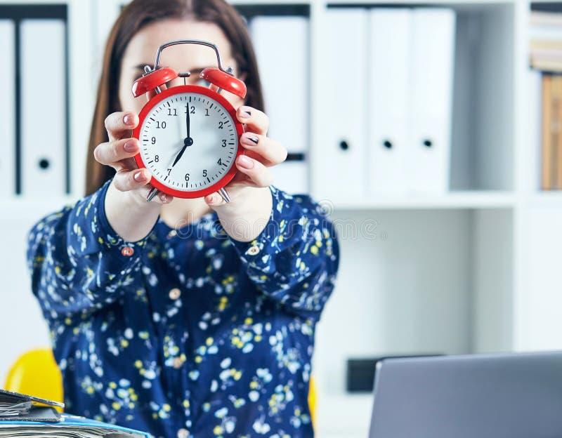 Weiblicher Büroangestellter, der einen großen roten Wecker vor ihrem Gesicht hält lizenzfreie stockfotografie