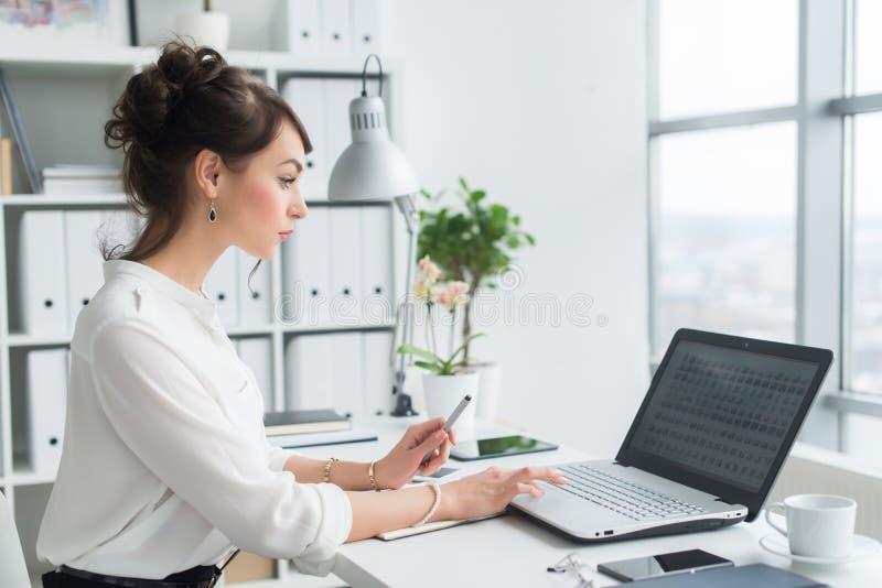 Weiblicher Büroangestellter, der Laptop an ihrem Arbeitsplatz, Graseninformationen, das Internet surfend, Seitenansichtporträt ve lizenzfreies stockbild