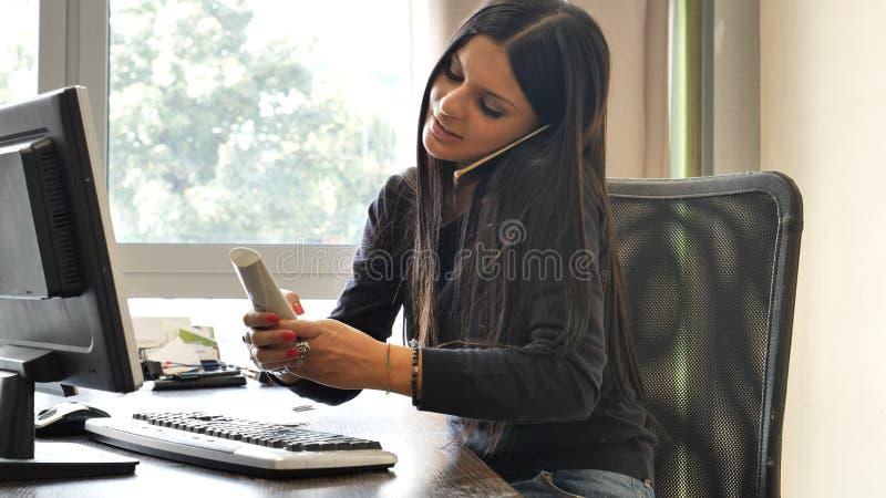 Weiblicher Büroangestellter, der am Schreibtisch beschäftigt mit zwei Telefonen sitzt lizenzfreies stockfoto