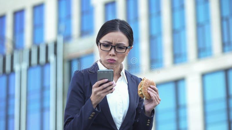 Weiblicher Bürovorsteher, der den ungesunden Burger überprüft Mitteilungen am Telefon, Druck isst lizenzfreies stockfoto