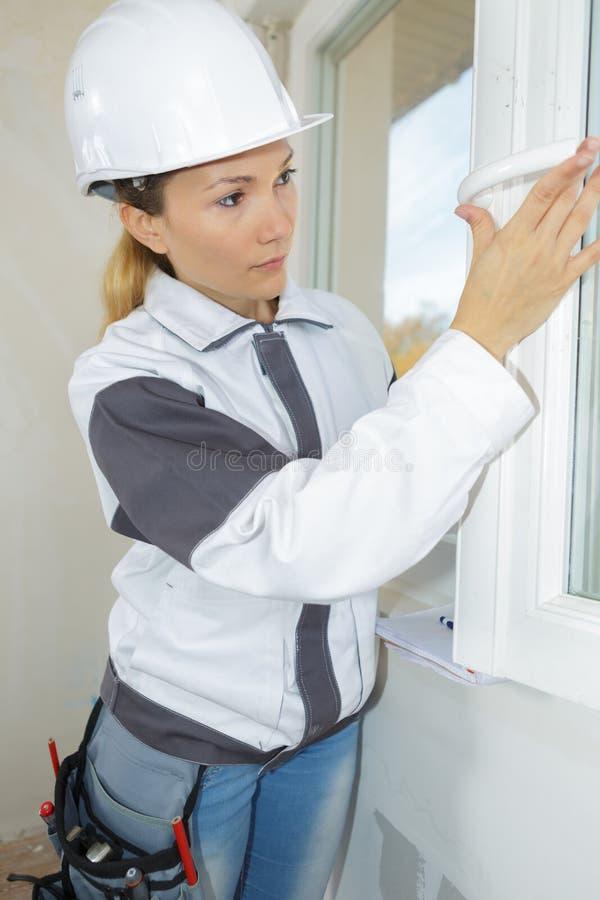 Weiblicher Bau, der an Fenster im Haus arbeitet stockfotos