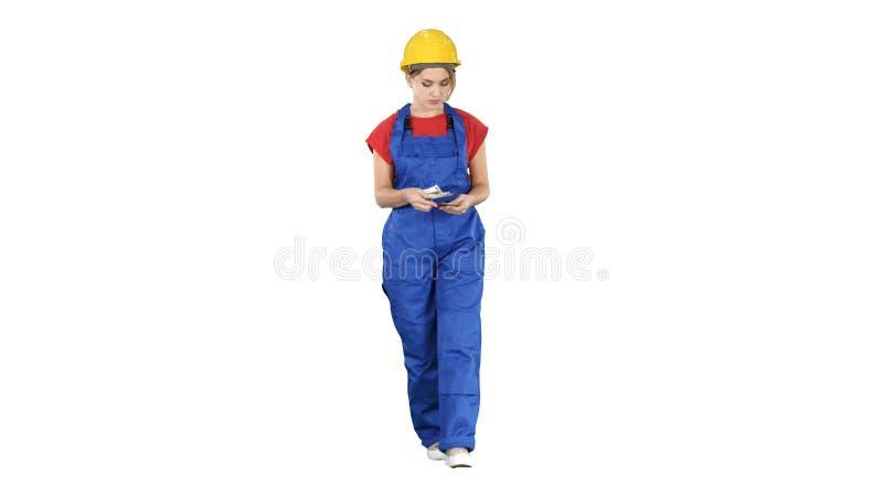 Weiblicher Bauarbeiter, der Geld beim Gehen auf wei?en Hintergrund z?hlt stockbilder