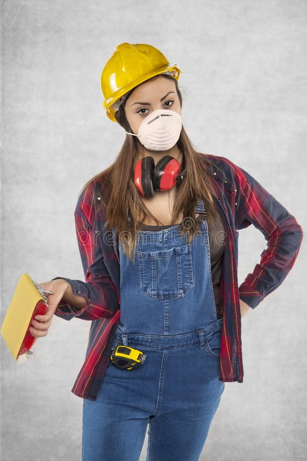Weiblicher Bauarbeiter, der Sandpapier hält stockfoto