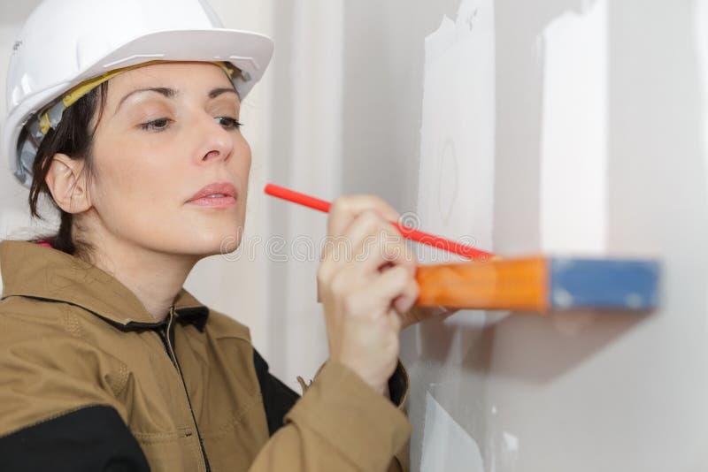 Weiblicher Bauarbeiter sorgfältig, der gerade hält stockbilder